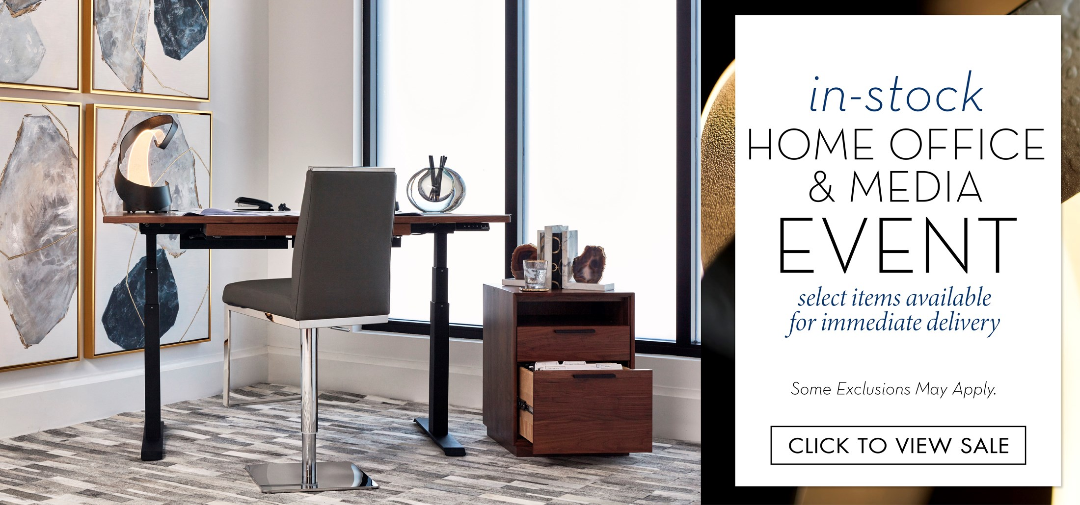 Image of a home office with a sit-stand desk. Text: In-Stock Home Office & Media Event. Select items available for immediate delivery. Some exclusions may apply. Click to view sale. Links to In-Stock Home Office & Media Event.