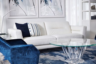 a photo of a living room vignette featuring a contemporary white leather sofa and a blue velvet chair