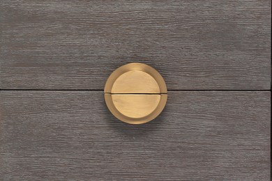 a photo of the front of a nightstand with focus on the wooden drawer fronts and brass drawer pull