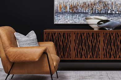 a photo of a tan leather chair with and industrial looking media cabinet accented with artwork and accessories